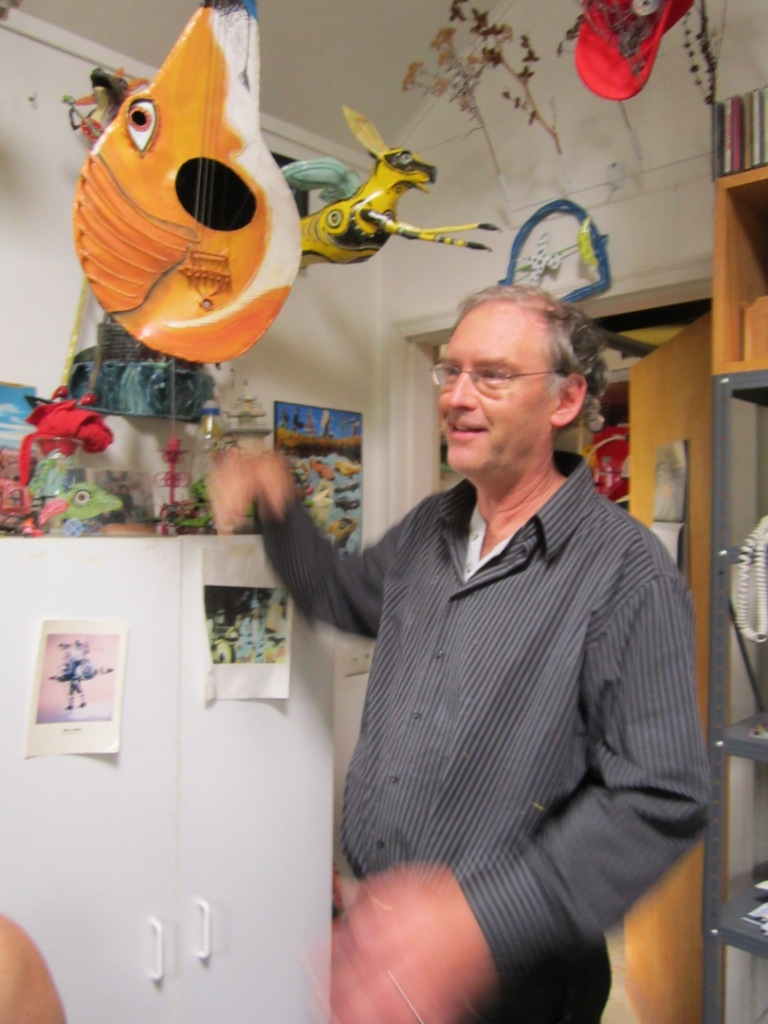 Bill Reid holding a musical sculpture in his home studio.