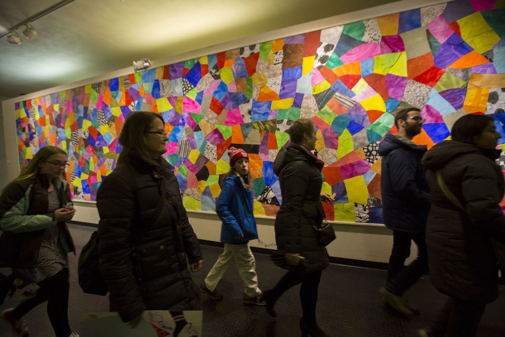 "People walk by a colorful collage by Michael Velliquette at an art installation called ""Municipal"" on Dec. 10, 2016.  PHOTO BY SAIYNA BASHIR"