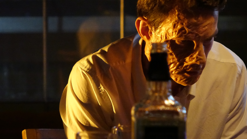 Oliver (Luke Cook) drinks his nightmare away.