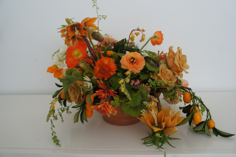 Low bowl tablecentre arrangement of flowers in orange colours
