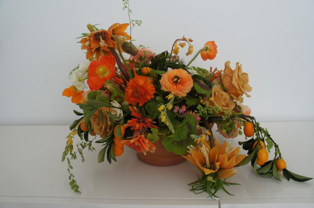 Low bowl tablecentre arrangement of flowers in orange colours