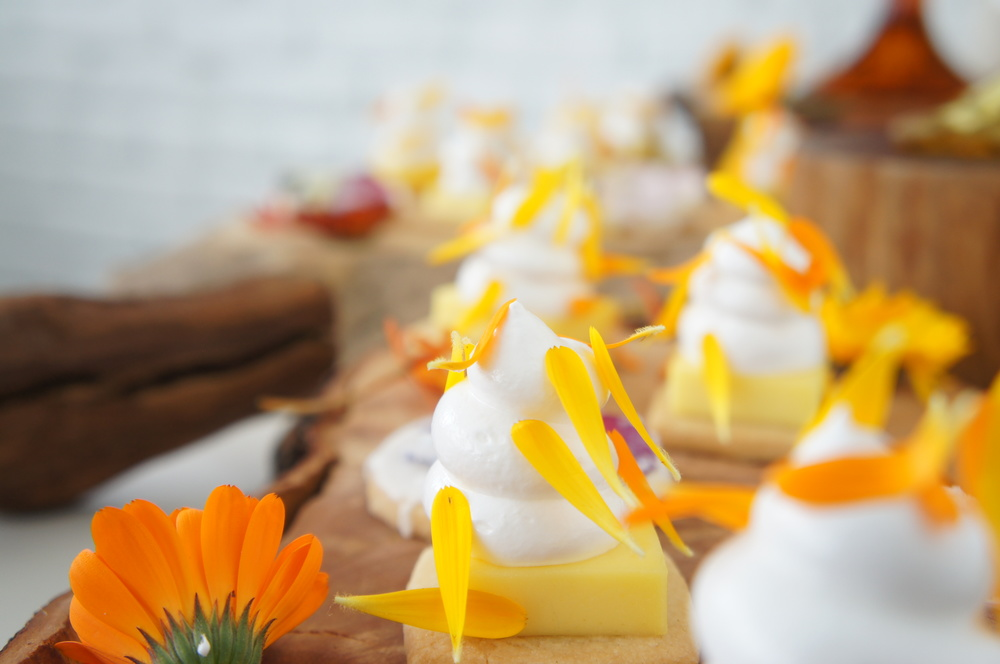 Mini Lemon Merigne Pie with flower petals on wooden board by Heirloom LA