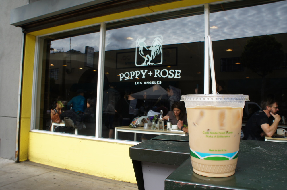 Iced coffee in takeaway cup in front of Poppy and Rose coffee shop in Los Angeles