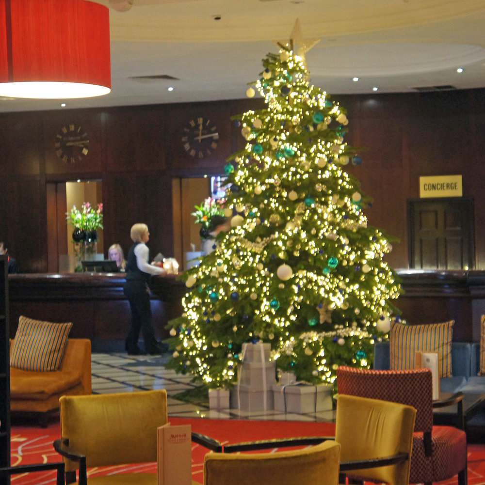 15ft real Christmas tree in Glasgow hotel lobby with fairy lights and decorations