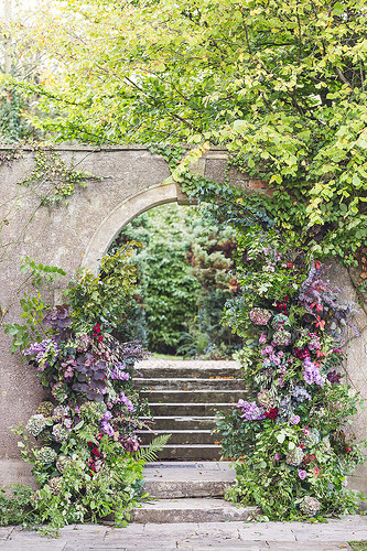Stone archway with flowers and foliage at Holbrook House
