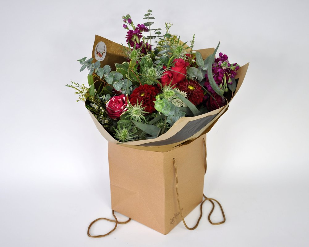 bouquet of flowers in brown paper bag ready for delivery