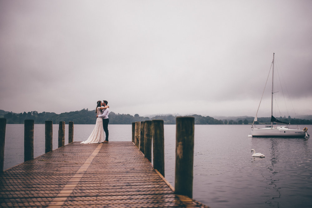 Cheshire wedding photographer captures bride and groom stood on the jetty at Langdale Chase Hotel in the Lake District.