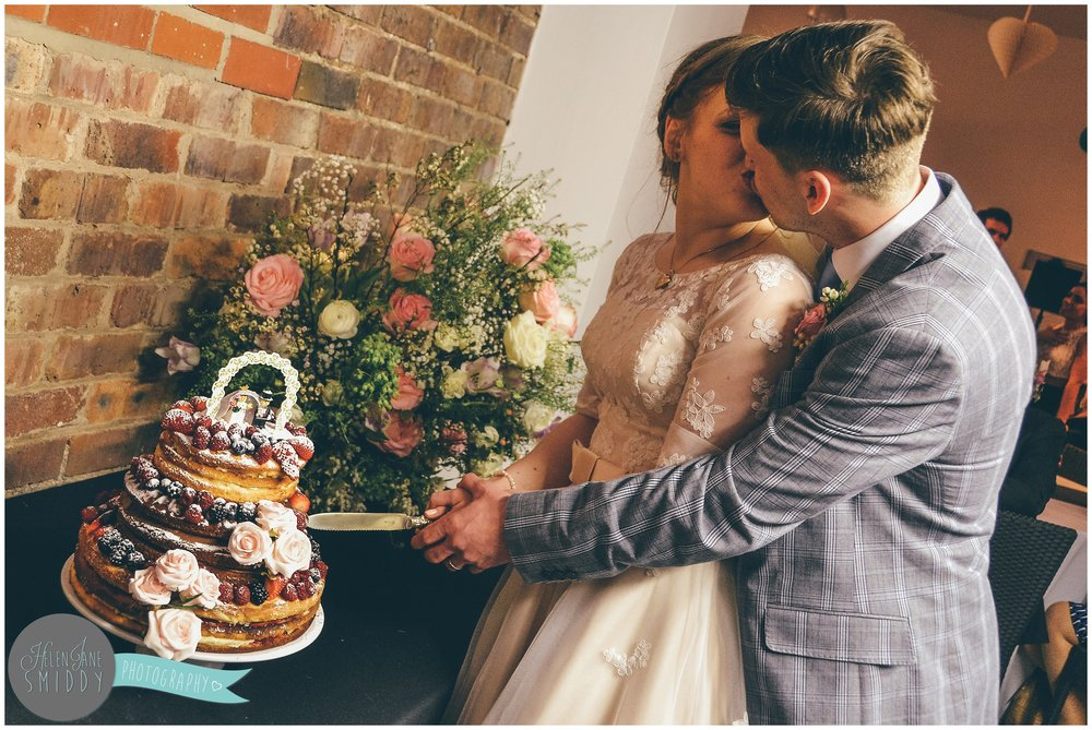 The bride and groom stole a kiss whilst cutting their wedding cake.