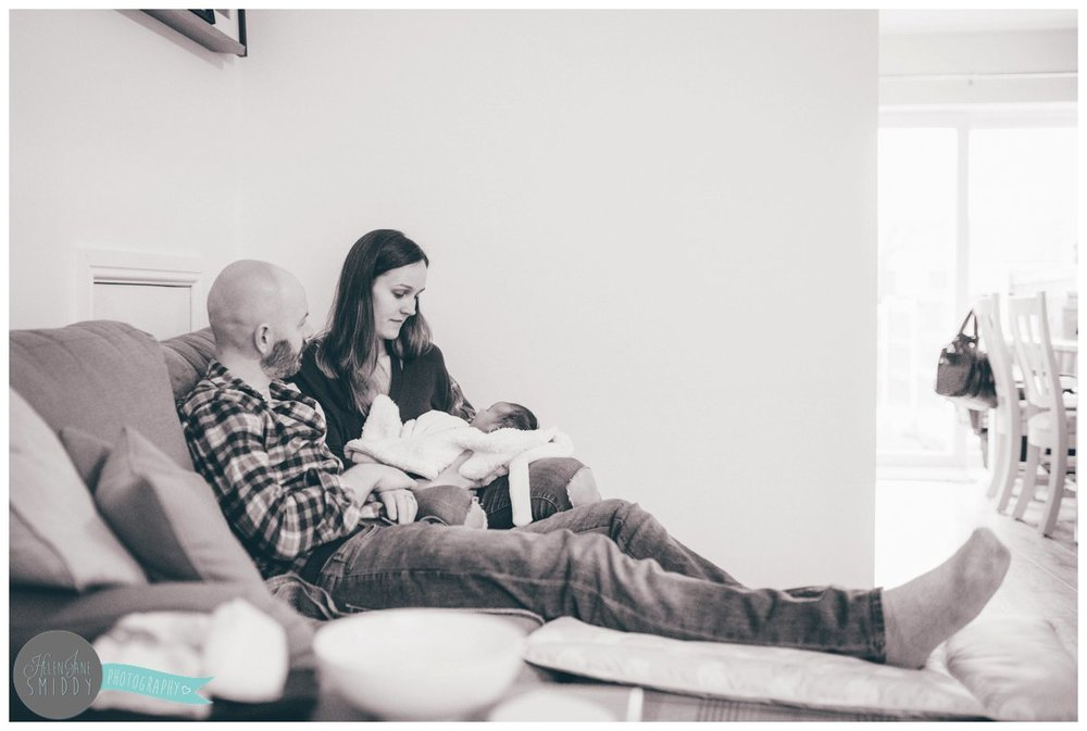 New Mum and Dad sit on the sofa in their living room in Frodsham, holding their newborn baby.