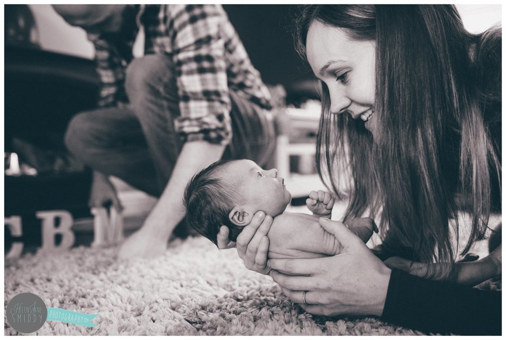Mother lays on the carpet with her newborn daughter whilst the dad lights a fire.
