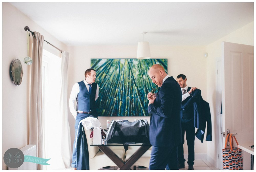 The groom arranges his hanky as his Best Man puts his suit jacket on and his usher smiles.