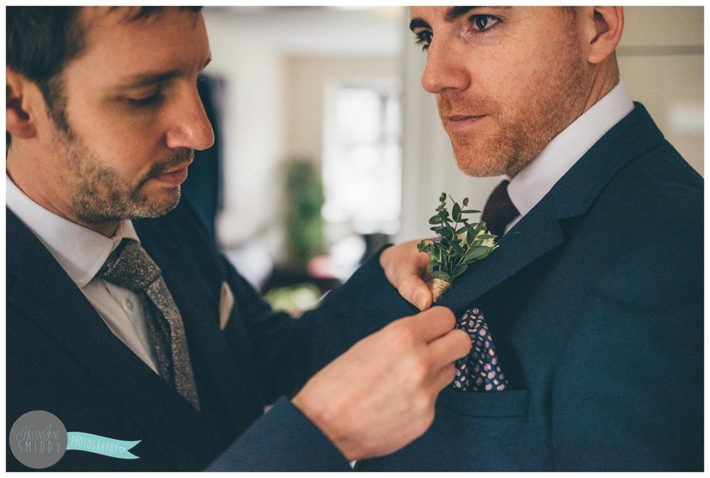 The groomsman fastens the pretty buttonhole onto the Groom's suit.