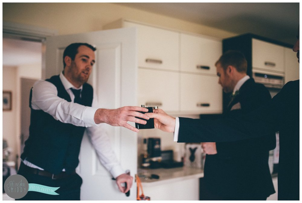 The groomsman passes the hip flask full of rum to his Best Man.