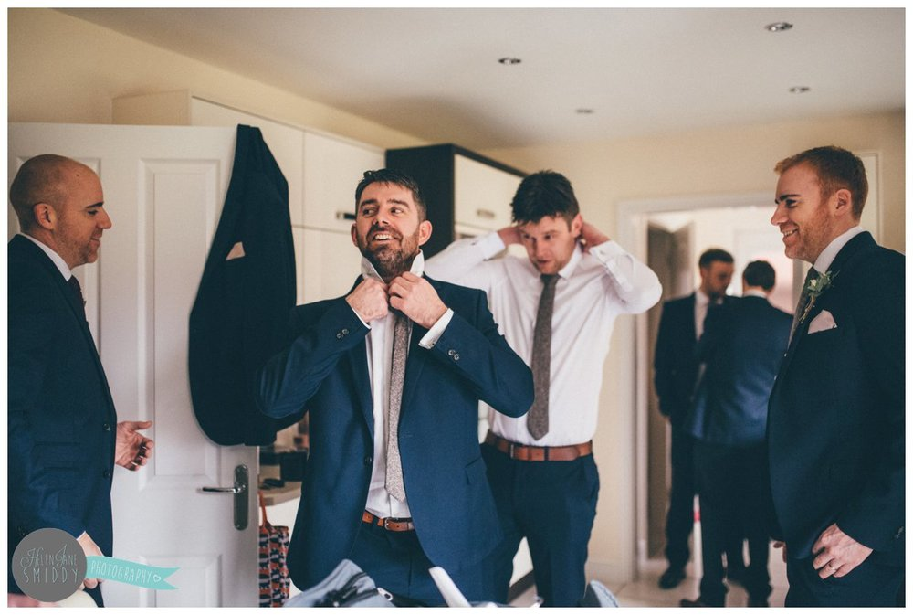 One of the groomsmen arrived late so laughs as he rushes to get ready.