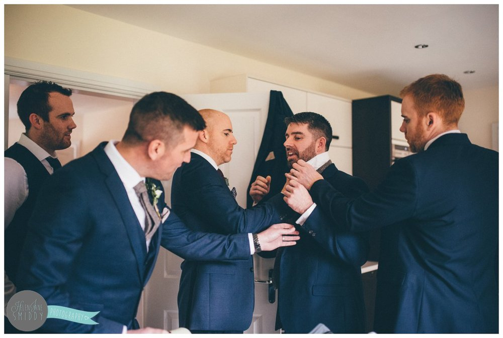 The groom and all the groomsmen all help their one friend tie his tie and sort out his suit.