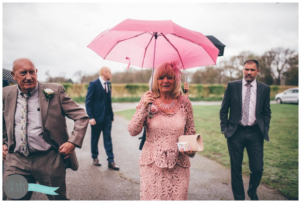 Pretty-in-pink wedding guestarrives with her pink umbrella to protect her from the rain.