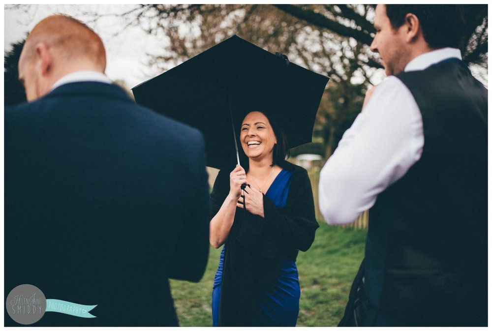Pretty wedding guest chats to the groom under her umbrella before the wedding ceremony.