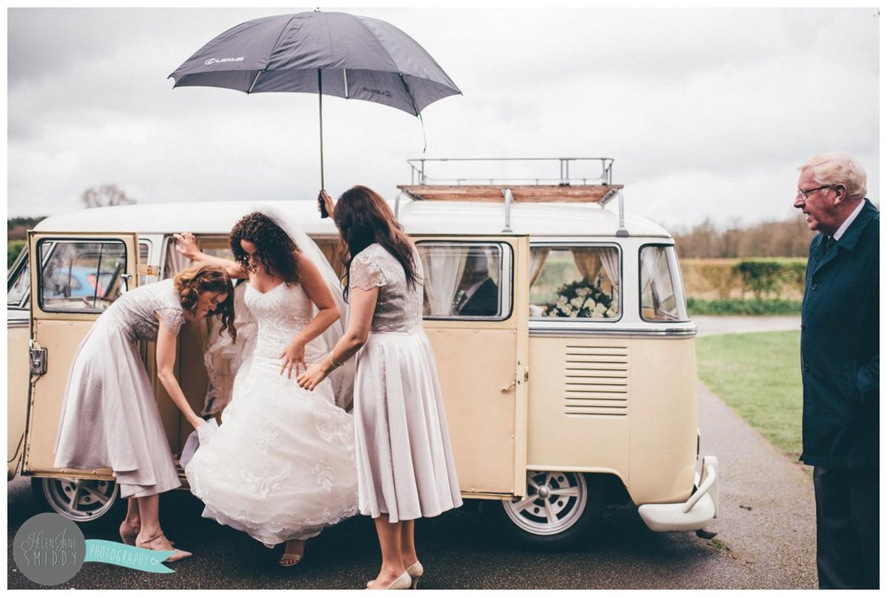 The bridesmaids help Lyssa, the bride arrange her dress and veil as she gets out of the camper van.