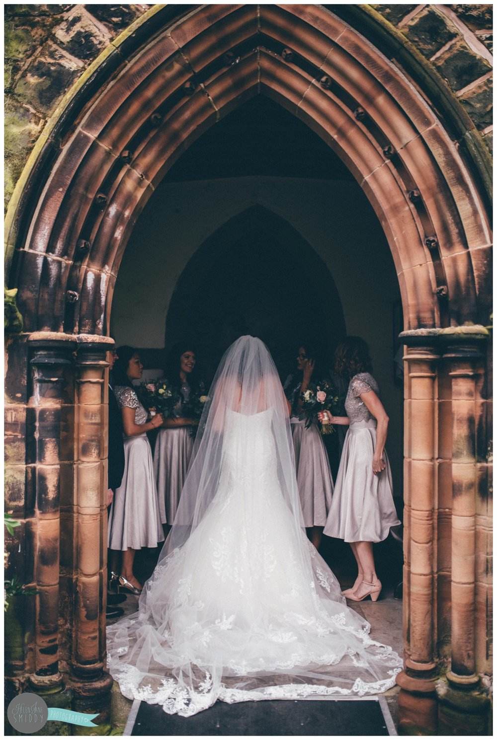 The back of the bride's beautiful Maggie Sottero gown as she stands in the archway at Toft Church in Knutsford.