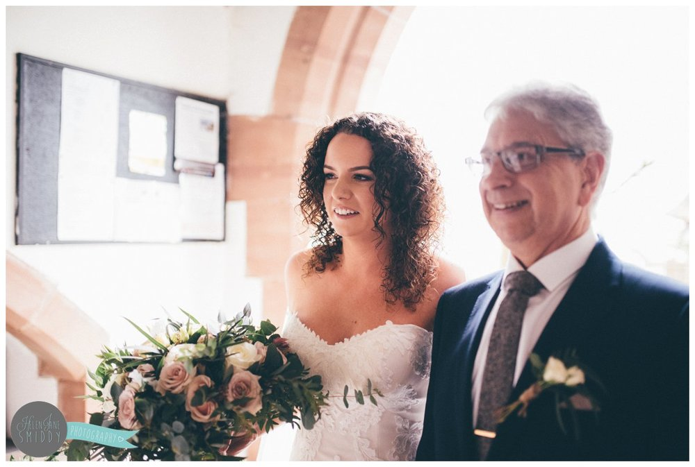 The bride smiles with her father before they walk down the aisle together.
