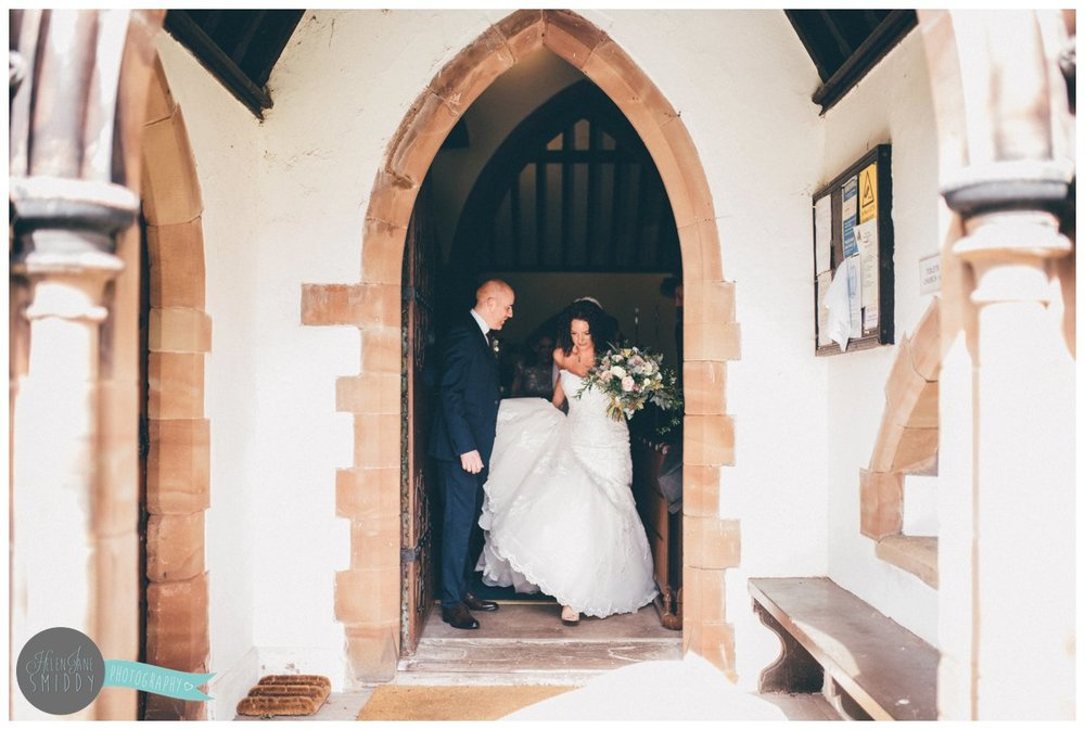 Bride and Groom leave Toft Church together whilst he helps her with her Maggie Sottero dress.