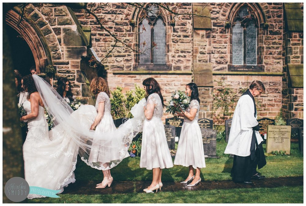 The vicar walks away from the bridal party after the wedding ceremony at Toft Church in Knutsford.