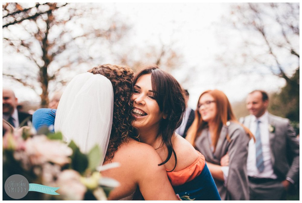 Pretty brunette hugs the bride and congratulates her.