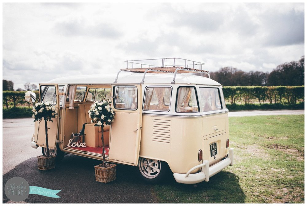 The wedding VW vintage camper van is parked in the sun whilst the bride and groom greet the wedding guests.