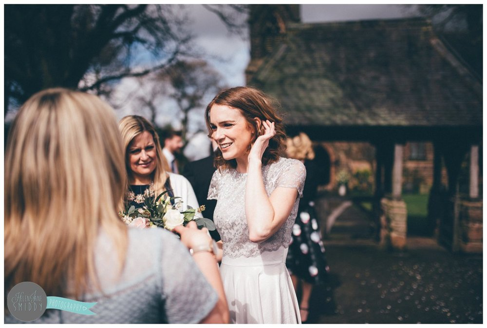 One of the bridesmaids chats to wedding guests after the wedding ceremony.