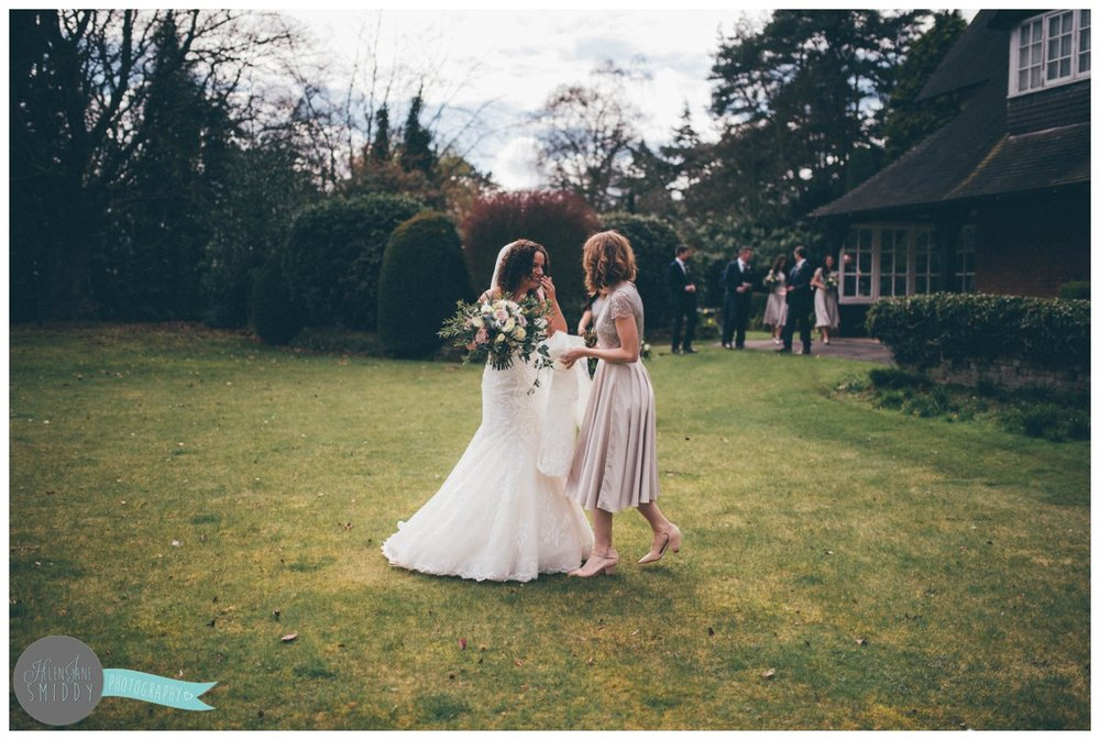 The beautiful bride and her best friend share a laugh as they walk across the lawn at Mere Court Hotel in Knutsford.
