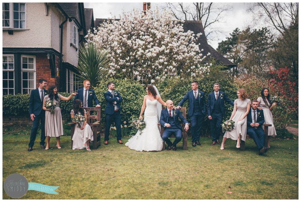 The bridal party have an informal wedding photograph at the Mere Court Hotel gardens in Knutsford.