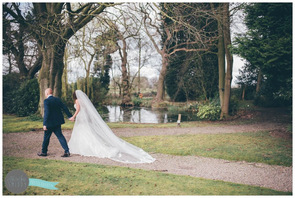 Lyssa's beautiful veil hangs perfectly as the bride and groom walk hand-in-hand outside at Mere Court Hotel.