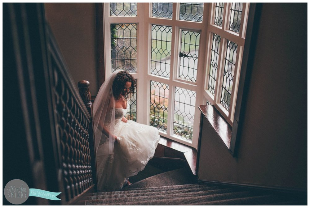 Lyssa holds her Maggie Sottero wedding gown as she walks up the stairs at Mere Court Hotel in Knutsford.
