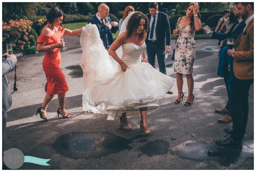 Lady in reed helps the bride protect her wedding gown from the puddles whilst the walk into Mer Court Hotel.