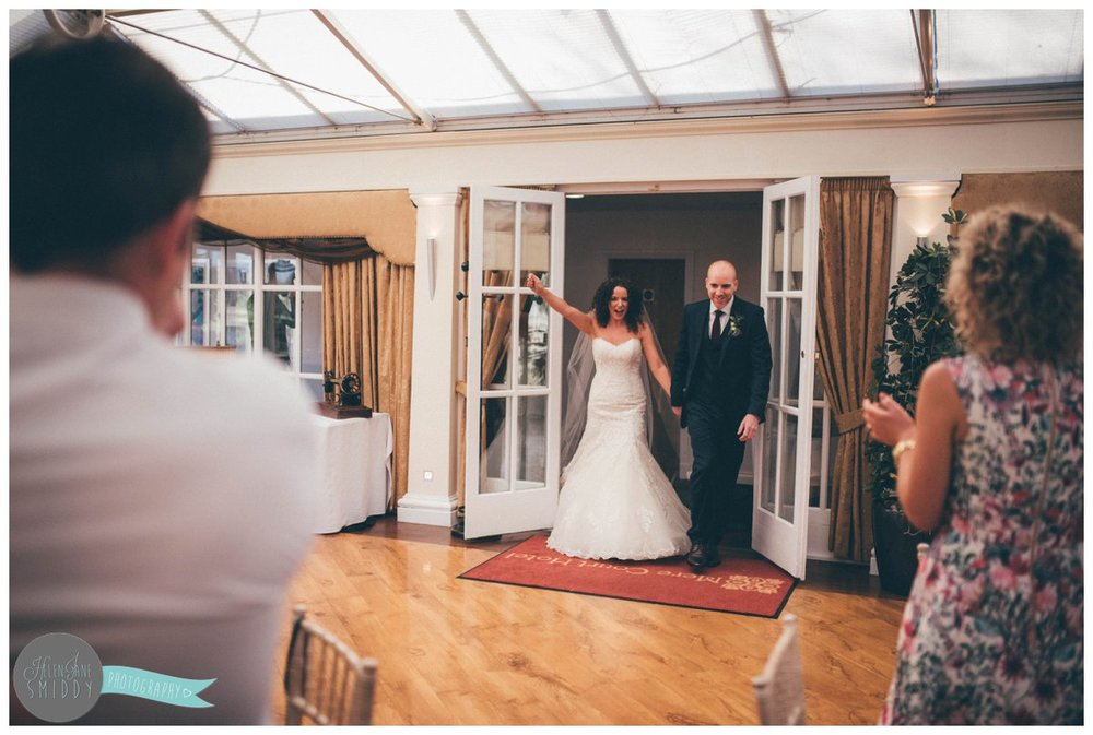 Lyssa cheers as her guests clap her and her new husband into the conservatory at Mere Court Hotel in Knutsford.