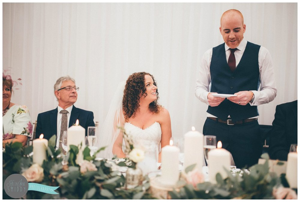 Lyssa looks at her new husband, smiling as he reds his wedding speech.