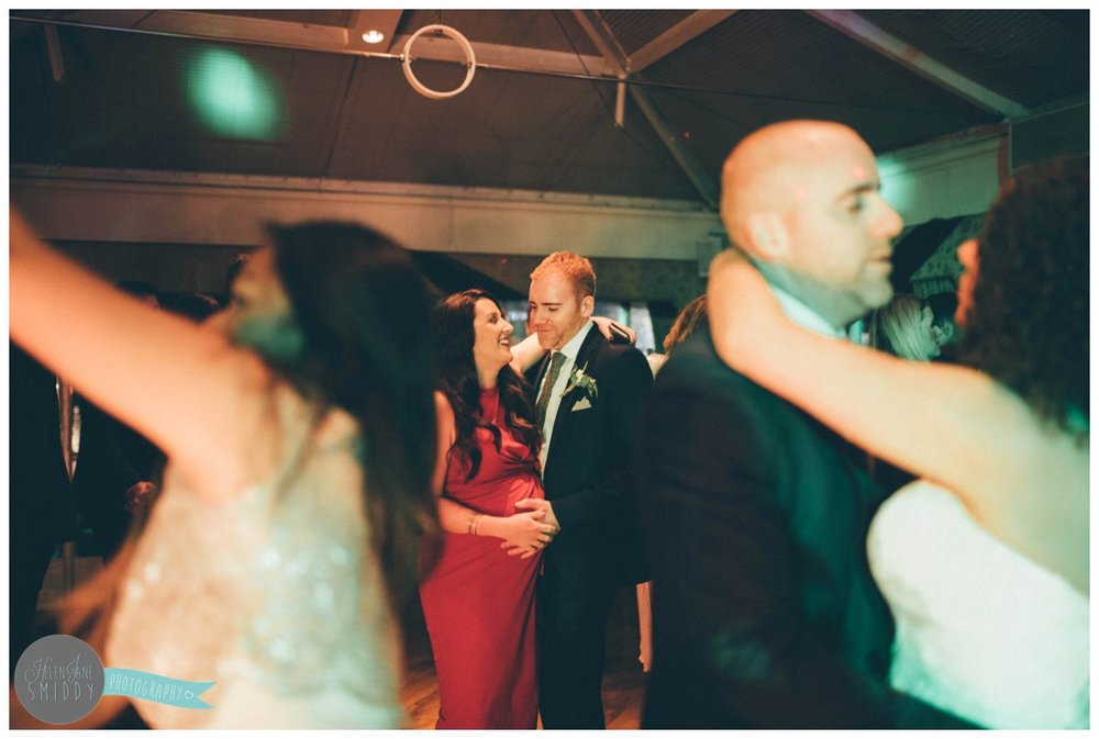 The pregnant wedding guest dances with her husband as he holds her stomach.