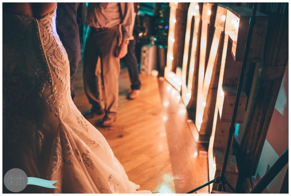 "The bride's gown is lit up by the beautiful ""love"" sign."