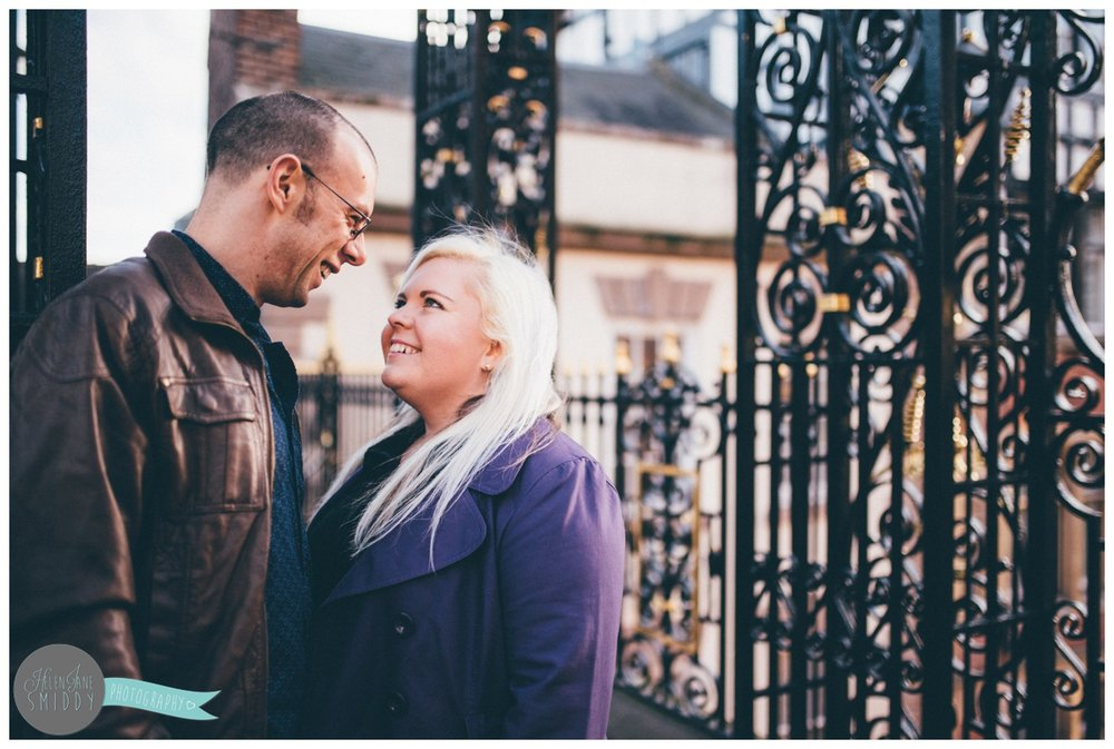 Couple stands underneath the Eastgate Clock in Chester, smiling at each other.