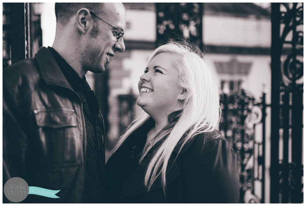 Close-up photograph of engaged couple underneath the Eastgate Clock in Chester, Cheshire.