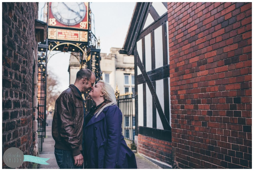 Young couple kiss on the bridge of the Eastgate Clock in Chester, Cheshire.
