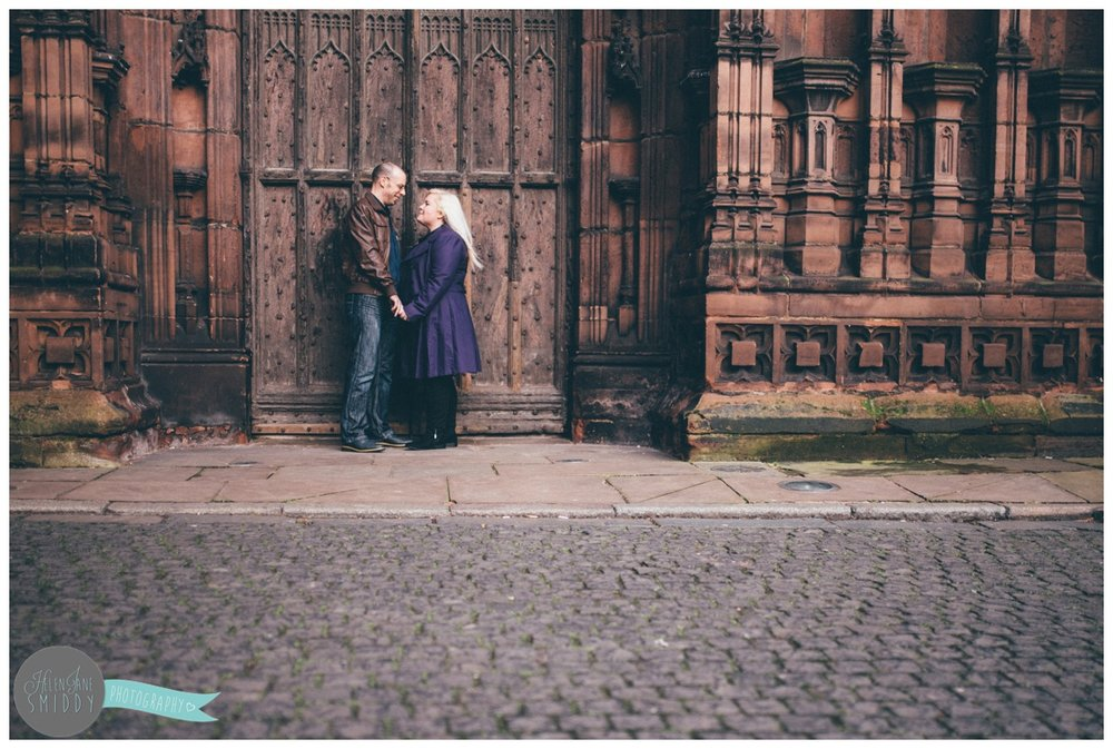 Couple face each other and hold hands, whilst stood in front of the beautiful big brown door of Chester Cathedral during their engagement shoot.