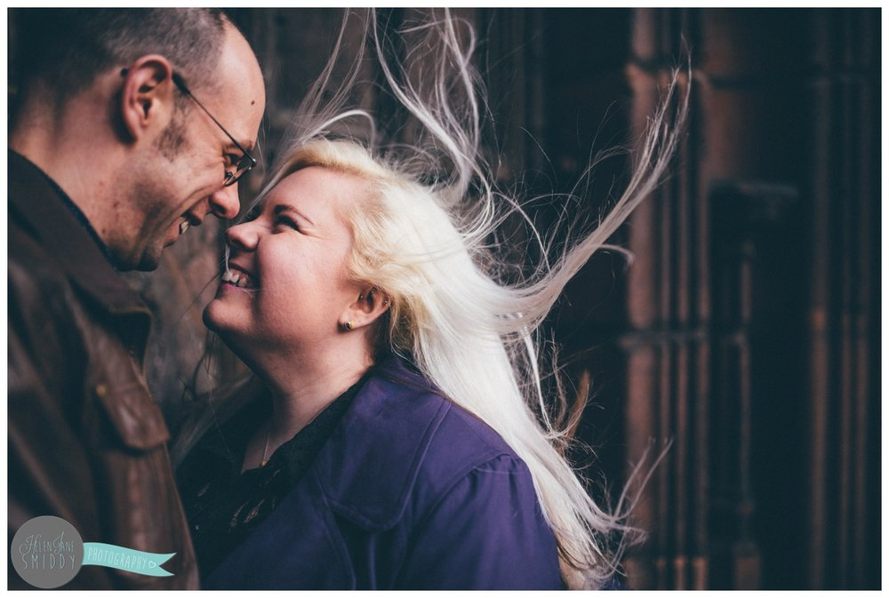 The wind blows the girl's hair as the couple face each other and hold hands, whilst stood in front of the beautiful big brown door of Chester Cathedral during their engagement shoot.