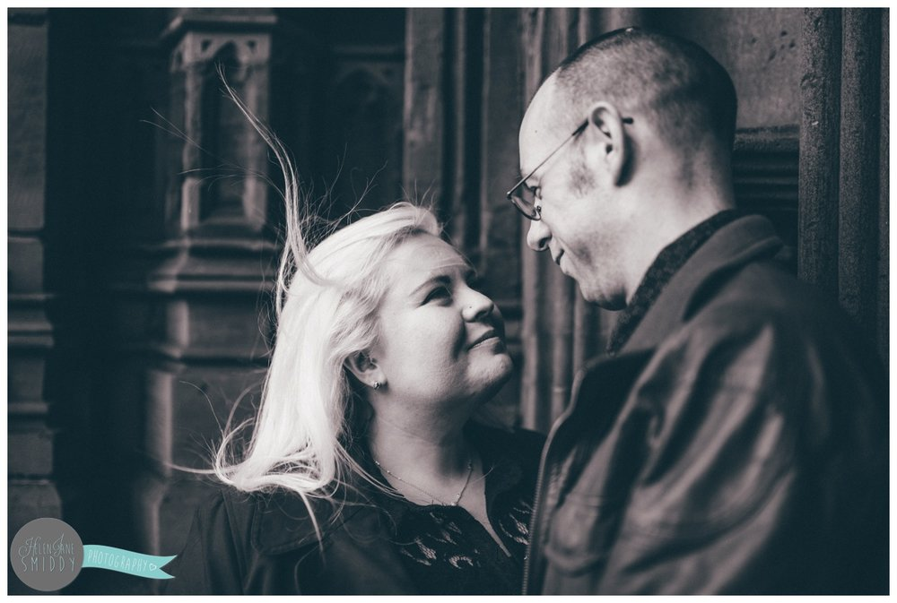Couple face each other and hold hands, whilst stood in front of the beautiful big brown door of Chester Cathedral during their engagement shoot in Chester City Centre.