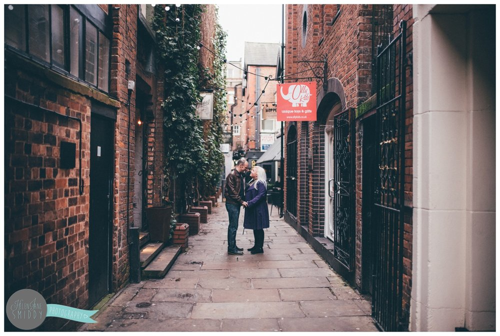 Joanna and Alan stand in the alleyway behind the Botanist in Chester for their engagement shoot.