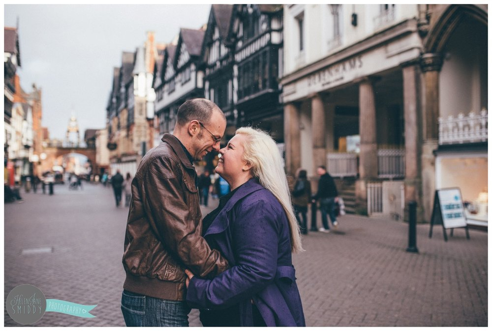 Jo and Alan stand, hugging and laughing in Chester City Centre for their engagement shoot.