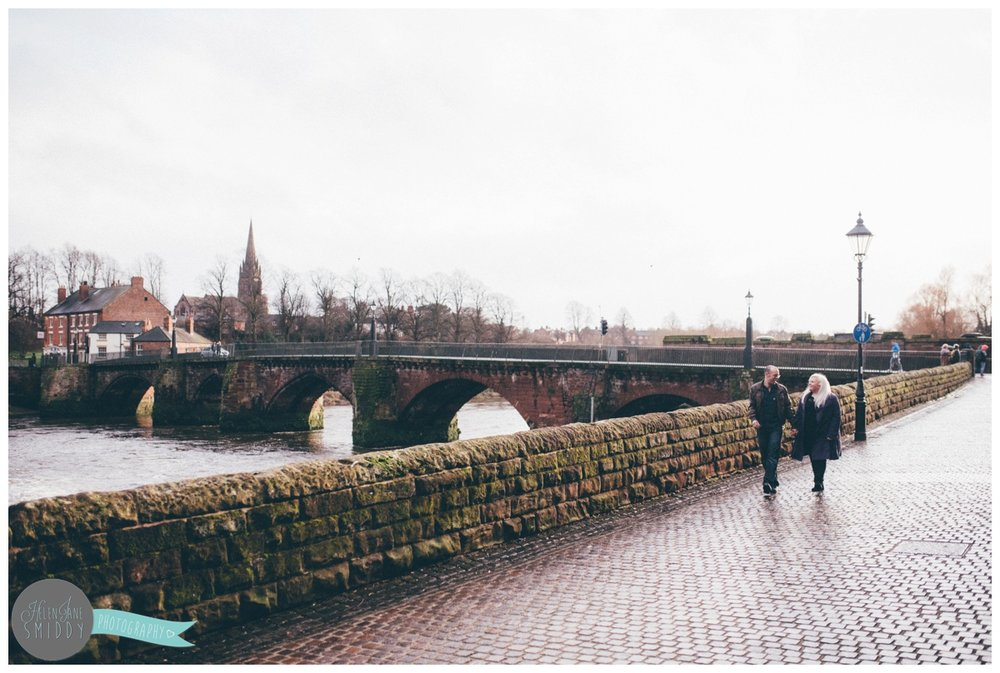 Joanna and Alan stroll, hand-in-hand along the River Dee in Chester, Cheshire for their pre-wedding shoot.