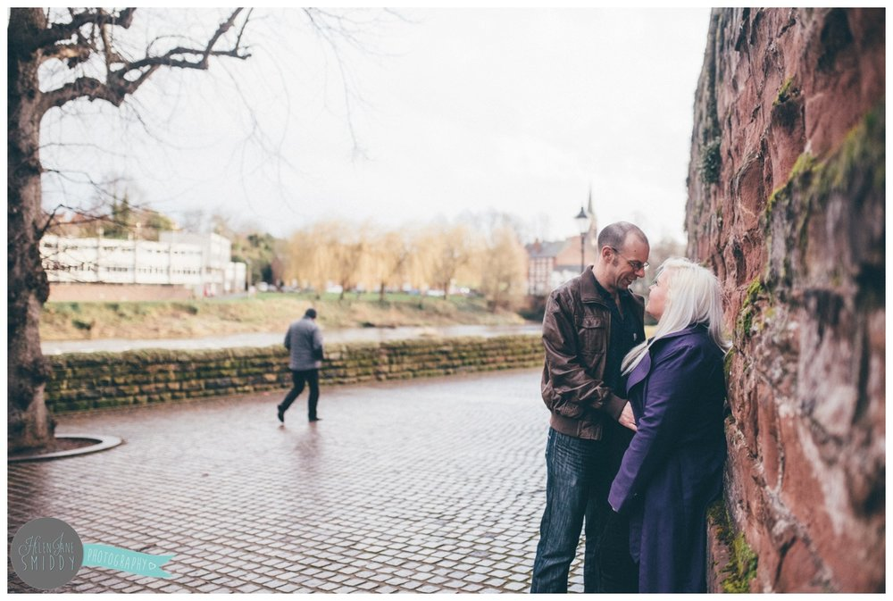 The couple stand against part of the old Roman walls next to the River Dee during their Engagement Shoot in Chester.