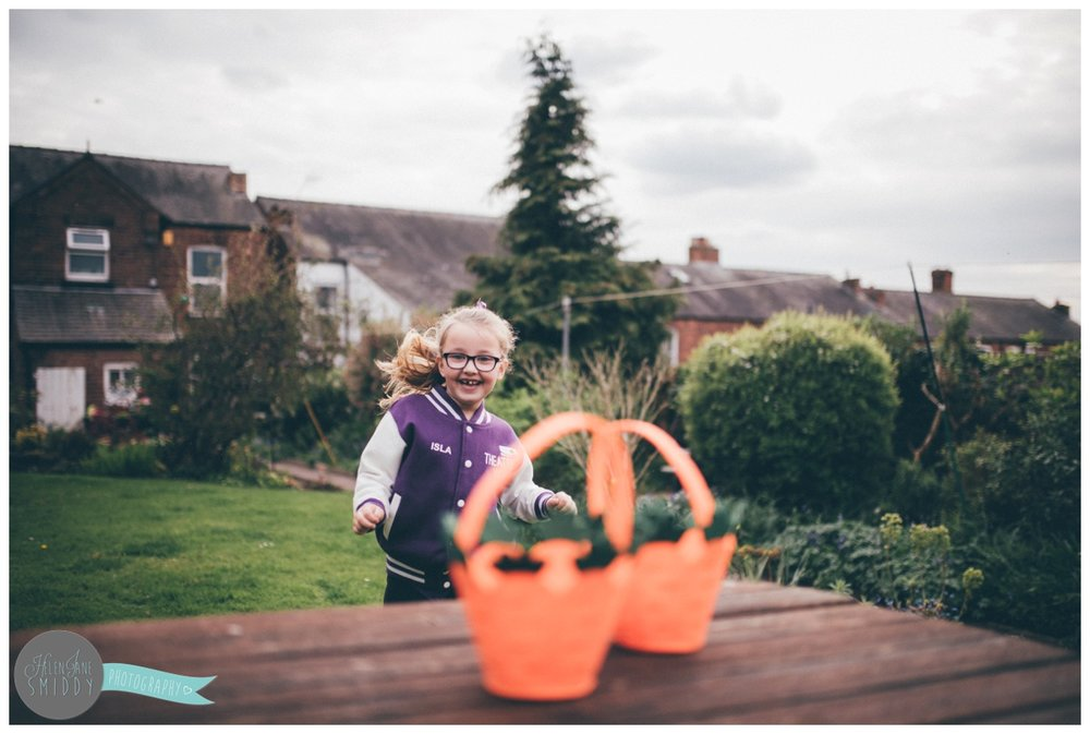 Little girl runs excitably towards the baskets for the Easter Egg hunt.