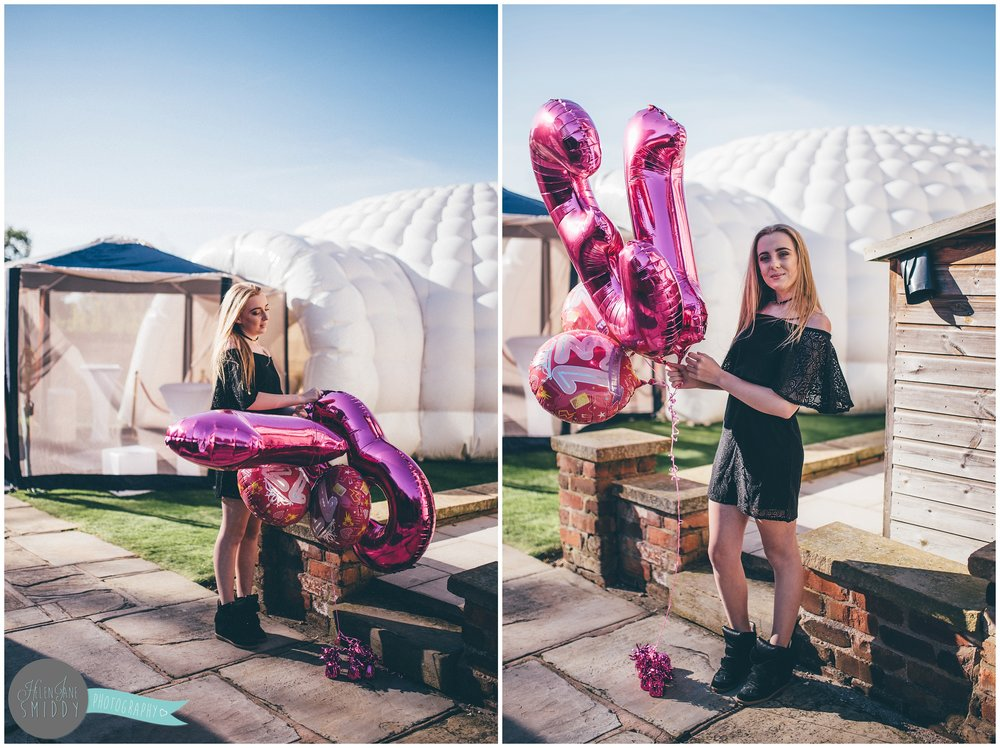 The birthday girl stood with her huge bright pink balloons.